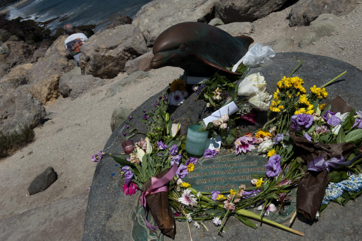 A man looks out into the ocean as he sits by a memorial placed for the victims of the Conception and people lost at sea at the Santa Barbara harbor on Wednesday, Sept. 4, 2019 in Santa Barbara, Calif. A fire raged through the boat carrying recreational scuba divers anchored near an island off the Southern California Coast on Monday, leaving multiple people dead. (AP Photo/Christian Monterrosa)