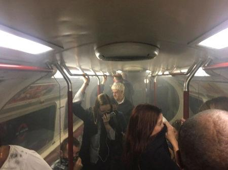 Passengers cover their faces as a carriage on a Bakerloo Line train starts to fill with smoke at Oxford Circus station in London