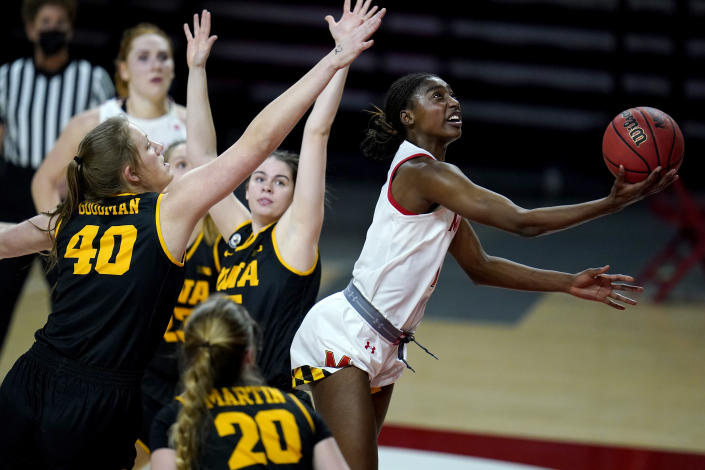 Maryland guard Diamond Miller, right, goes up for a shot against Iowa center Sharon Goodman (40), guard Kate Martin (20) and guard Lauren Jensen, center, during the second half of an NCAA college basketball game, Tuesday, Feb. 23, 2021, in College Park, Md. Maryland won 111-93. (AP Photo/Julio Cortez)