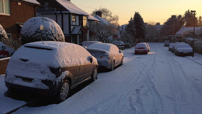 Cars parked on snow covered pavement in Grove Park London