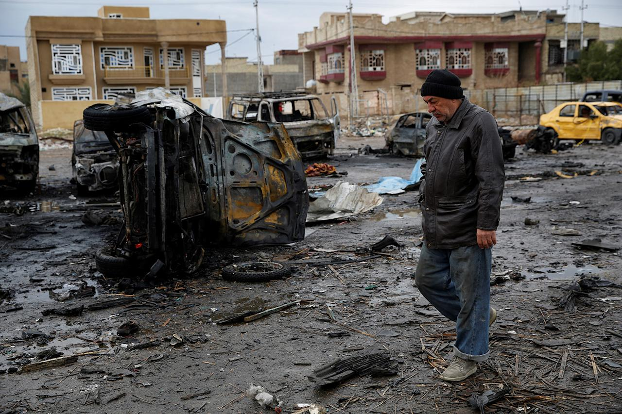<p>A man walks past the wreckage of cars a day after a car bomb attack at al-Bayaa auto gallery in capital of Baghdad, Iraq on February 17, 2017. Many casualities reported after the attack. (Photo by Murthadha Sudani/Anadolu Agency/Getty Images) </p>