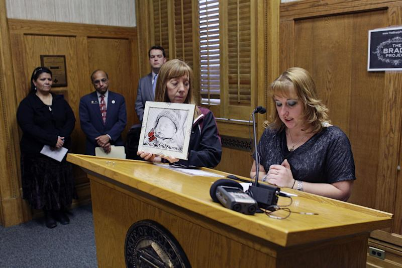 """Heather Surovik, right, who miscarried after the car she was driving in was struck by chronic drunken driver Gary Sheats in in 2012, speaks during a news conference promoting a political drive to grant """"personhood"""" status to unborn fetuses, at the Colorado State Capitol, in Denver, Colo., Monday Jan. 28, 2013. At center is Surovik's mother, Terry Koester, holding a photographic rendering of Surovik's fetus following the miscarriage. (AP Photo/Brennan Linsley)"""