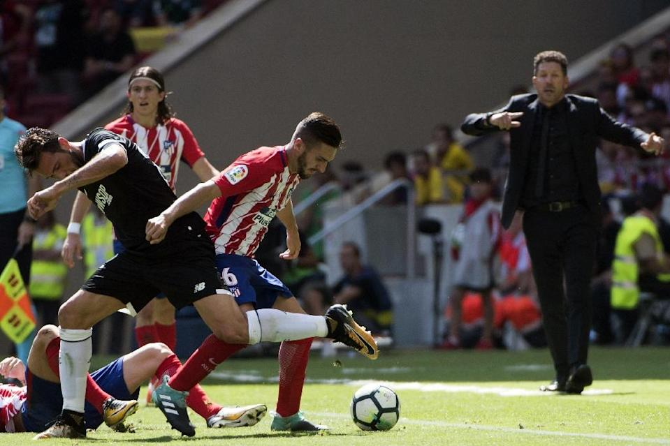 Atletico Madrid's head coach Diego Simeone (R) gestures as Sevilla's Franco Vazquez (L) fights for the ball with Atletico's Koke during their Spanish La Liga match, at the Wanda Metropolitano stadium in Madrid, on September 23, 2017 (AFP Photo/CURTO DE LA TORRE)