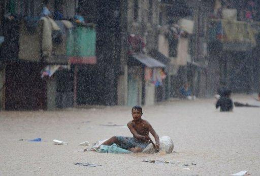 A resident paddles an improvised raft in heavy rain in suburban Manila on August 8, 2012. Philippine authorities appealed Thursday for volunteers to help deliver food, water and other relief goods to two million people affected by deadly floods in and around the Philippine capital
