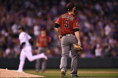 Jul 11, 2018; Denver, CO, USA; Arizona Diamondbacks relief pitcher Daniel Descalso (3) watches as Colorado Rockies right fielder Carlos Gonzalez (5) (background) rounds the bases in the fourth inning at Coors Field. Mandatory Credit: Ron Chenoy-USA TODAY Sports