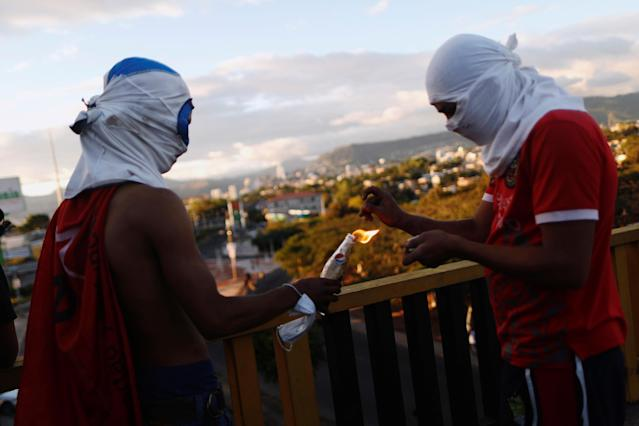 <p>Supporters of presidential candidate Salvador Nasralla light a Molotov cocktail during a protest caused by the delayed vote count for the presidential election at Villanueva neighborhood in Tegucigalpa, Honduras, Dec. 1, 2017. (Photo: Edgard Garrido/Reuters) </p>