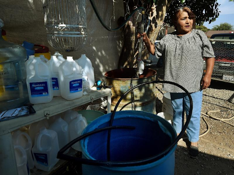 Maria Jimenez demonstrates how they pump bottled water up to a storage tank on the roof of their rented house to wash in the drought affected town of Monson, California on June 23, 2015 (AFP Photo/Mark Ralston)