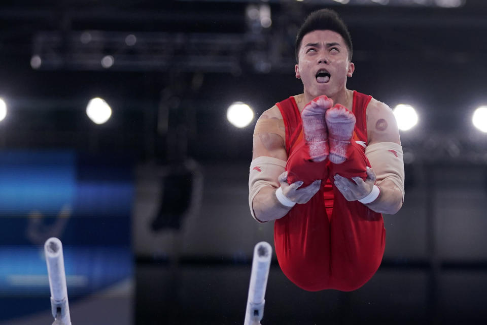China's Lin Chaopan performs on the parallel bars during the men's artistic gymnastic qualifications at the 2020 Summer Olympics, Saturday, July 24, 2021, in Tokyo. (AP Photo/Gregory Bull)
