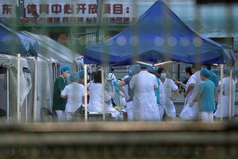 Medical workers gather at Beijing's Dongdan sports centre to conduct COVID-19 tests