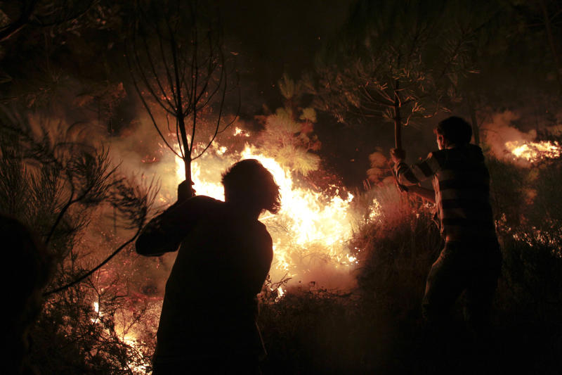 People using branches of trees help to extinguish a fire in Tondela, near Viseu, Portugal, Thursday night, Aug. 22, 2013. Portuguese authorities said one firefighter has died and six were injured as they battled a wildfire in Tondela. (AP Photo/Francisco Seco)