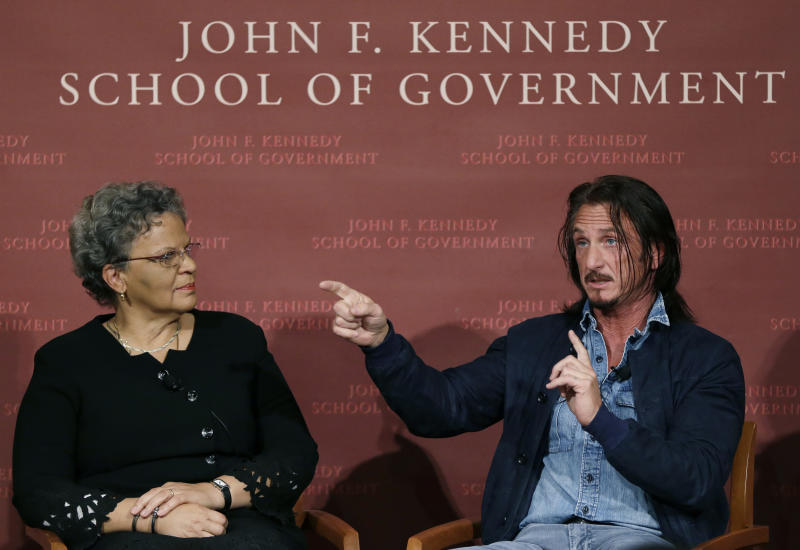 Actor-director Sean Penn gestures as he speaks, while the former prime minister of Haiti, Michele Pierre-Louis, listens while they participate in a discussion at Harvard University's John F. Kennedy School of Government in Cambridge, Mass. Tuesday, Feb. 26, 2013 regarding Haiti in the wake of a devastating earthquake three years ago. Penn is the co-founder of the J/P Haitian Relief Organization. (AP Photo/Elise Amendola)