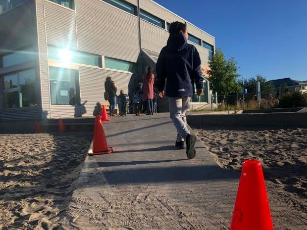 Students head back to class at Weledeh Catholic School in Yellowknife in August. Kandola said she's talking with education officials about whether public health restrictions will need to remain in place for the rest of the school year.