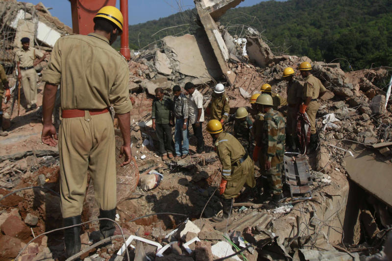 Rescue workers look at a body stuck in the debris of a building that collapsed in Canacona, about 70 kilometers (44 miles) from Goa state capital Panaji, India, Sunday, Jan. 5, 2014. The five-story building under construction in the southern Indian state of Goa collapsed on Saturday, killing at least a dozen people and leaving dozens more feared trapped under the rubble, police said. (AP Photo/Rafiq Maqbool)