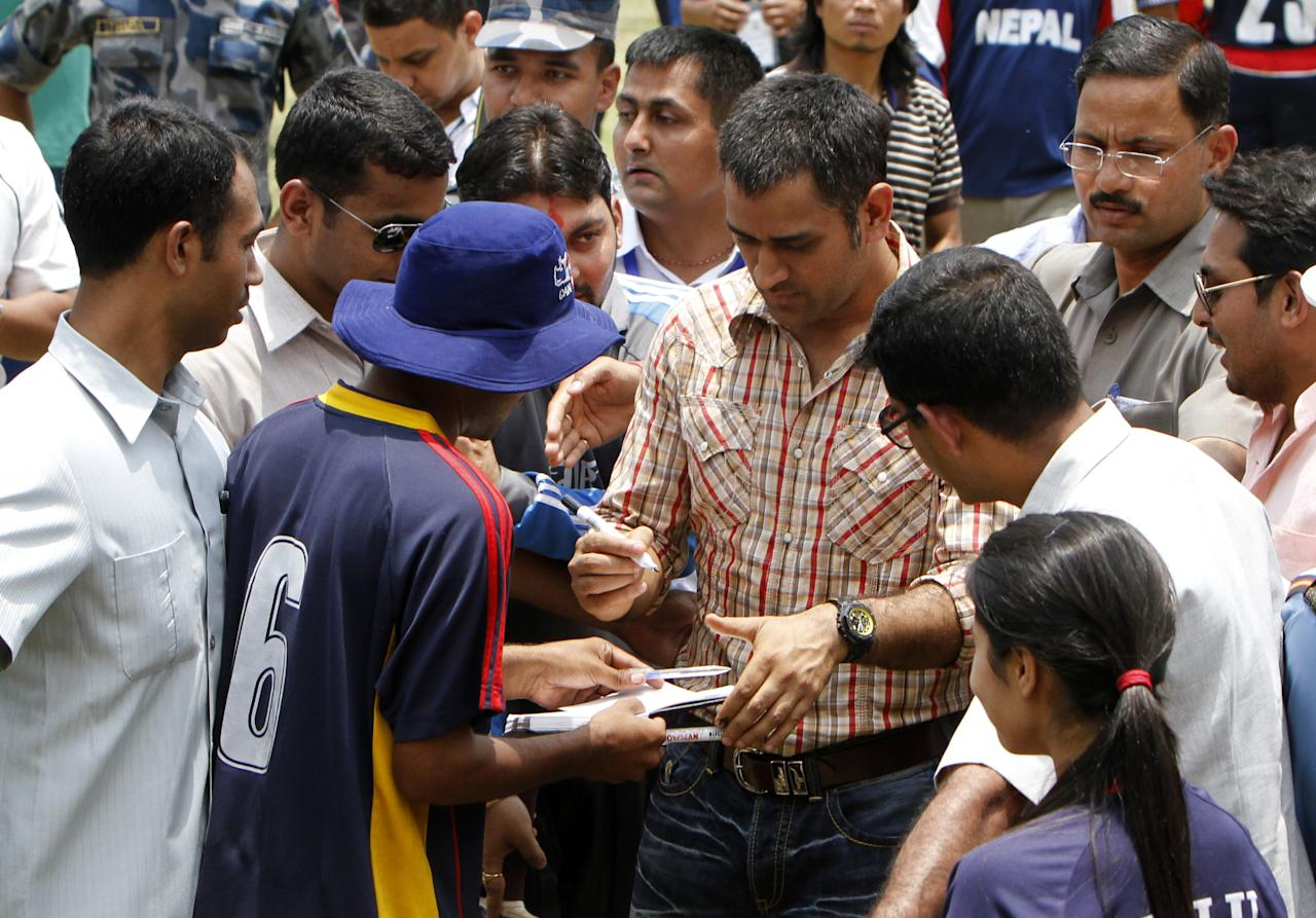 Indian cricket team captain Mahendra Singh Dhoni (R) signs autographs while meeting the Nepali cricket team at Tribhuvan University Cricket ground in Kathmandu on 16, June 2012. Dhoni arrived in Nepal for a one day visit. AFP PHOTO/ STR        (Photo credit should read STR/AFP/GettyImages)