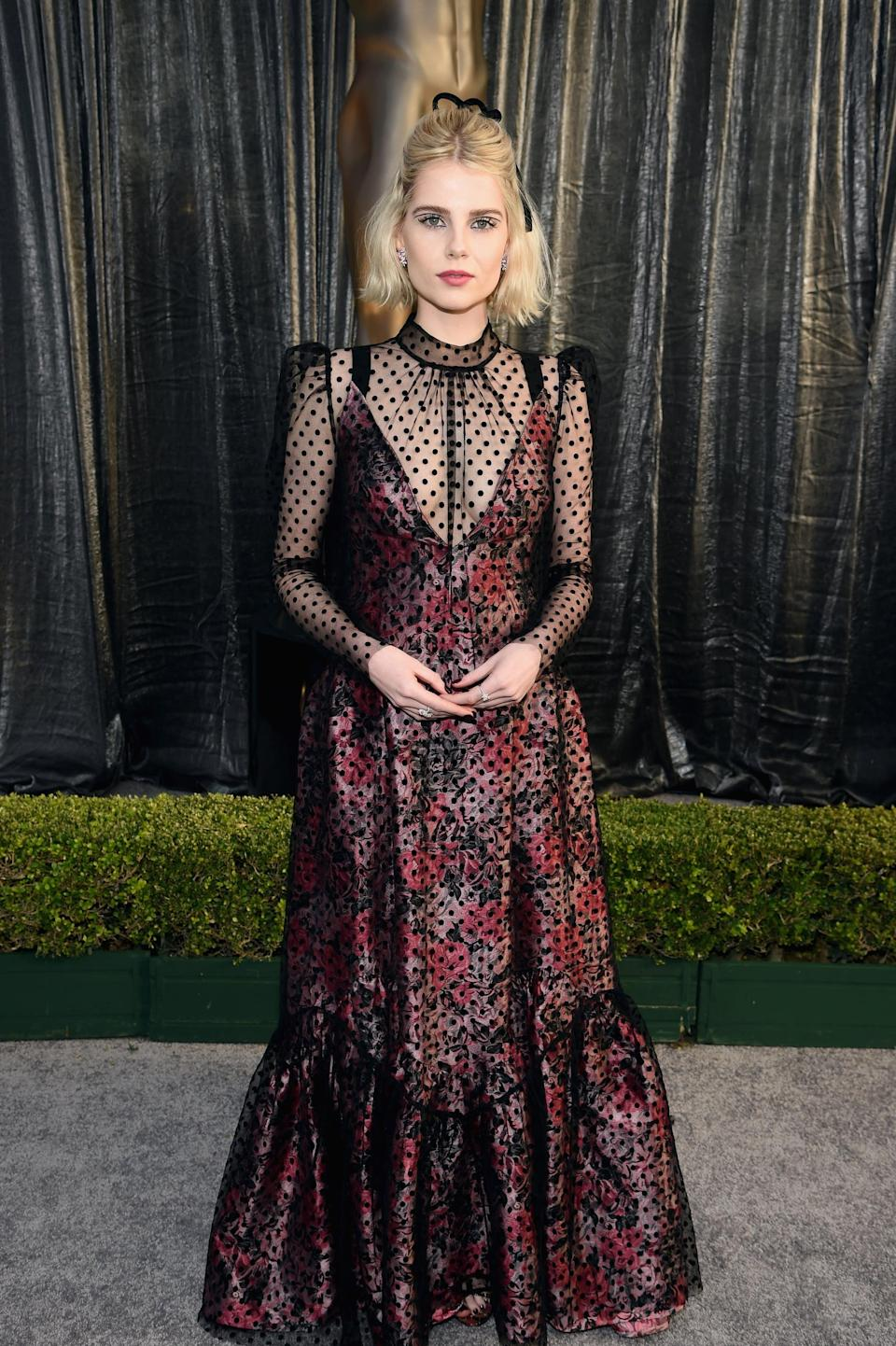 <p>Wearing a sheer net and floral Erdem gown with Harry Winston jewels.</p>