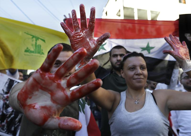 Lebanese pro-Syrian regime supporters with their hands painted in red to symbolize blood, attend a demonstration against a possible military strike in Syria, near the U.S. Embassy in Awkar, east of Beirut, Lebanon, Friday, Sept. 6, 2013. The prospect of a U.S.-led strike against Syria has raised concerns of potential retaliation from the Assad regime or its allies. The State Department ordered nonessential U.S. diplomats to leave Lebanon over security concerns and urged private American citizens to depart as well. The yellow flag represents Hezbollah, as the Syrian flag is seen at right. (AP Photo/Hussein Malla)