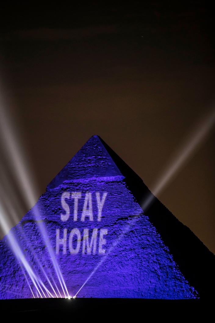 "A picture on April 18, 2020, shows the Great Pyramids lit in blue with the message ""Stay Home"" outside the Egyptian capital of Cairo."