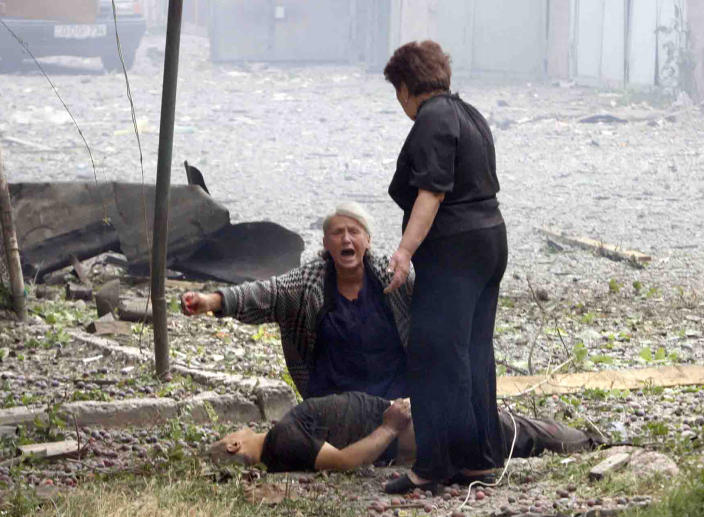 FILE - In this Saturday, Aug. 9, 2008 file photo, a Georgian woman cries near a body after a Russian airstrike in the northern Georgian town of Gori. The European Court of Human Rights ruled Thursday, Jan. 21, 2021 that Russia was responsible for a swathe of violations in Georgia's breakaway regions after the 2008 Russia-Georgia war. (AP Photo/George Abdaladze, File)