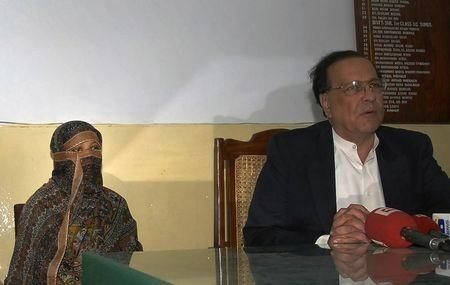 A Pakistani Christian woman who has been sentenced to death for blasphemy sits next to Governor of the Punjab Province as he talks to media after visiting her inside the central jail in Sheikhupura