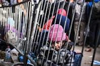 A young girl sits behind a barrier with other migrants and refugees waiting near the registration camp outside the town of Presevo on October 21, 2015, after crossing the Macedonian-Serbian border (AFP Photo/Armend Nimani)