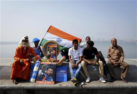 A cricket fan dressed as a Hindu holy man, or Sadhu, sits next to portraits of Indian cricketer Sachin Tendulkar outside a stadium in Mumbai November 16, 2013. Tendulkar did not get a chance to bat again in his final test but India's 'Little Master' was allowed to bowl a couple of overs on Saturday before drawing his 24-year glittering career to an emotional conclusion. REUTERS/Danish Siddiqui