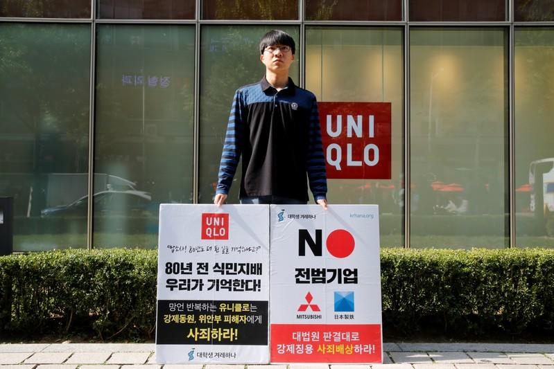 A university student Bang Seulkichan stands with banners as a protest against recent released Uniqlo commercial in front of a Uniqlo store in Seoul