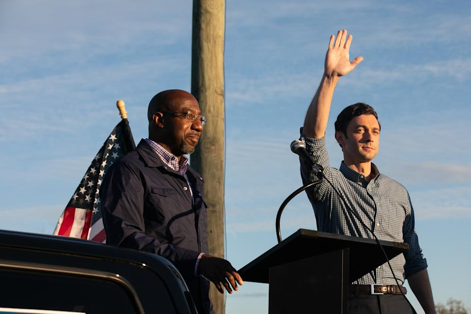 Georgia Democratic U.S. Senate candidates Jon Ossoff (R) and Raphael Warnock (L) wave to supporters during a rally on November 15, 2020 in Marietta, Georgia. (Jessica McGowan/Getty Images)