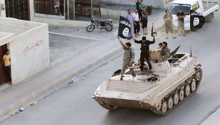 Militant Islamist fighters take part in a military parade along the streets of northern Raqqa province