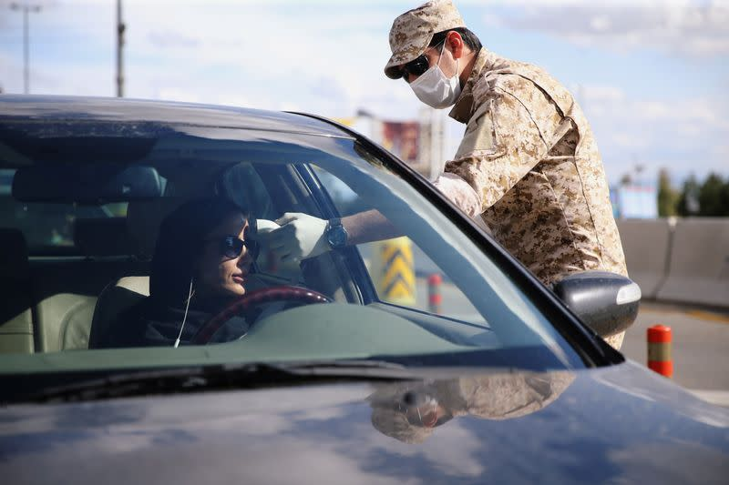 A member of the Islamic Revolution Guards Corps (IRGC) troops measures a temperature, following the outbreak of coronavirus disease (COVID-19) at the entrance of Qom