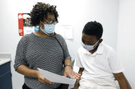 Jeremiah Young, 11, right, listens as Dr. Janice Bacon, a primary care physician, with Central Mississippi Health Services in Hinds County, explains the necessity of receiving inoculations prior to attending school, Aug. 14, 2020, while at the Community Health Care Center on the Tougaloo College campus in Tougaloo, Miss. Bacon and the staff of medical and mental health care professionals, provide personalized care to a population that is overwhelmingly Black and where there have been the most positive cases of coronavirus reported in the state. (AP Photo/Rogelio V. Solis)
