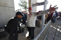 A fan entering Bryant Denny Stadium is checked for weapons by a uniformed Secret Service officer before an NCAA football game between Alabama and LSU Saturday, Nov. 9, 2019, in Tuscaloosa, Ala. President Donald Trump is expected to attend. (AP Photo/John Bazemore)