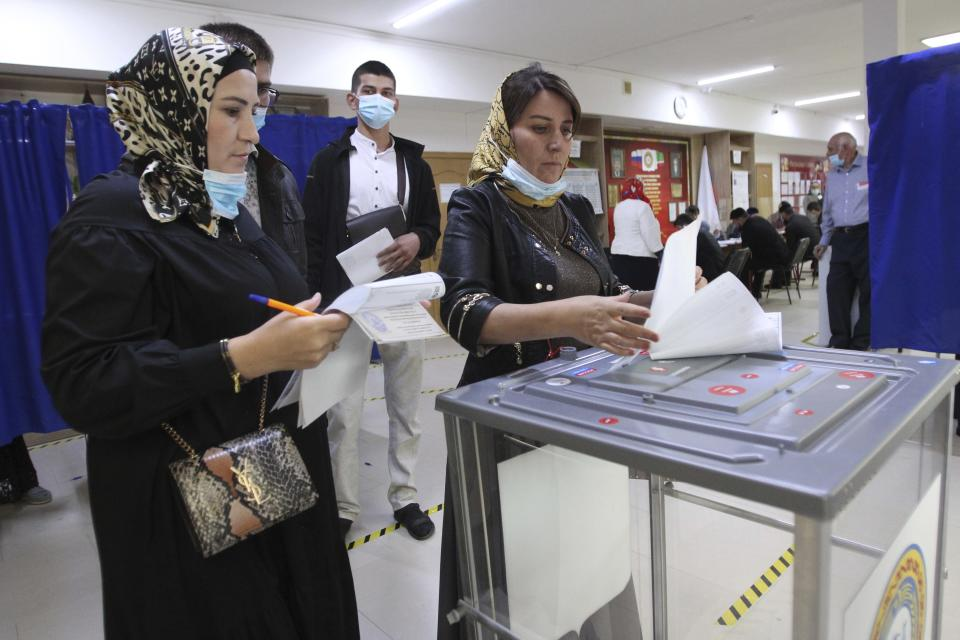 Chechen women cast their ballots at a polling station during the Parliamentary elections in Grozny, Russia, Friday, Sept. 17, 2021. Russia has begun three days of voting for a new parliament that is unlikely to change the country's political complexion. There's no expectation that United Russia, the party devoted to President Vladimir Putin, will lose its dominance in the State Duma. (AP Photo/Musa Sadulayev)