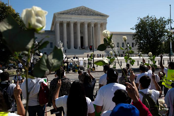 Mourners hold up white roses for Justice Ruth Bader Ginsburg at the steps of the U.S. Supreme Court Sept. 23.