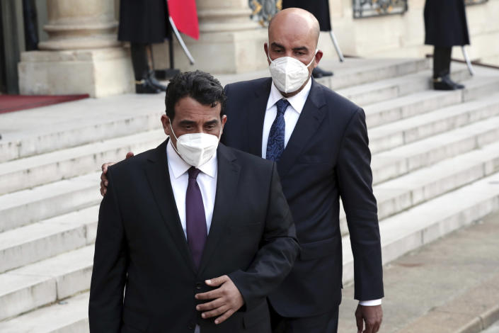 Mohammad Younes Menfi, president of Libya's Presidential Council, left, and Musa al-Koni, vice-president of Libya's Presidential Council arrive to deliver a speech at the end of a meeting, at the Elysee Palace, in Paris, Tuesday, March 23, 2021. Macron said France will reopen its embassy in Libya's capital Tripoli on Monday as a gesture of support for the new interim government. (AP Photo/Thibault Camus)