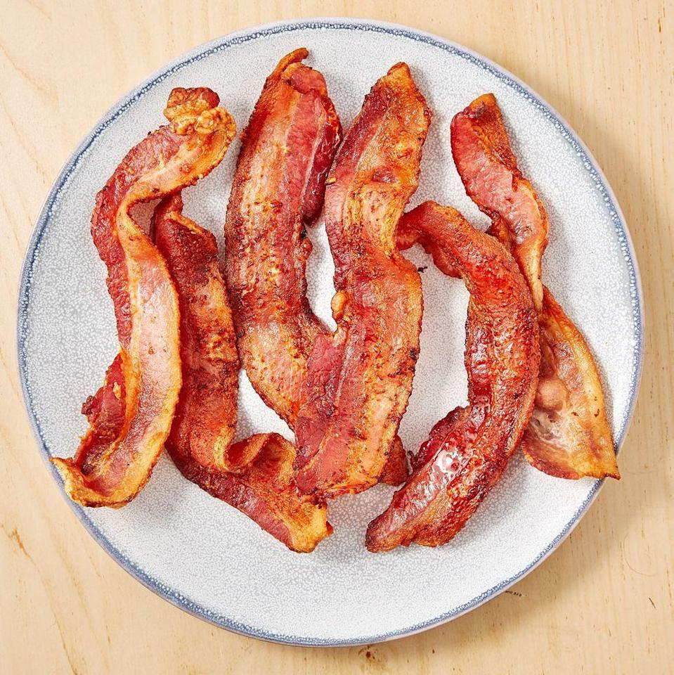 """<p><a href=""""https://www.delish.com/uk/cooking/recipes/a30208165/how-to-cook-bacon-in-the-oven-recipe/"""" rel=""""nofollow noopener"""" target=""""_blank"""" data-ylk=""""slk:Cooking bacon in the oven"""" class=""""link rapid-noclick-resp"""">Cooking bacon in the oven</a> is the classic move, and it's a great one, but we are here to tell you to give the air fryer a chance. It will be done faster than your oven can preheat and we are always looking for faster ways to bacon! The air fryer makes the crispiest bacon of all time without all of the crazy amounts of grease. You'll love yourself for it. </p><p>Get the <a href=""""https://www.delish.com/uk/cooking/recipes/a31424224/air-fryer-bacon-recipe/"""" rel=""""nofollow noopener"""" target=""""_blank"""" data-ylk=""""slk:Air Fryer Bacon"""" class=""""link rapid-noclick-resp"""">Air Fryer Bacon</a> recipe.</p>"""