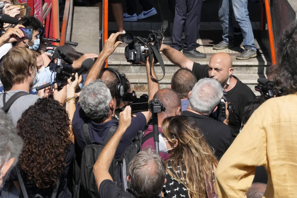 A demonstrator, right, shouts to reporters in Stazione Centrale central train station, Wednesday, Sept. 2, 2021, in Milan, Italy. Italy's government vowed to crack down on demonstrators threatening to block train tracks throughout the country Wednesday as a rule requiring COVID-19 tests or vaccines to use public transportation for long-distance domestic travel took effect. (AP Photo/Luca Bruno)