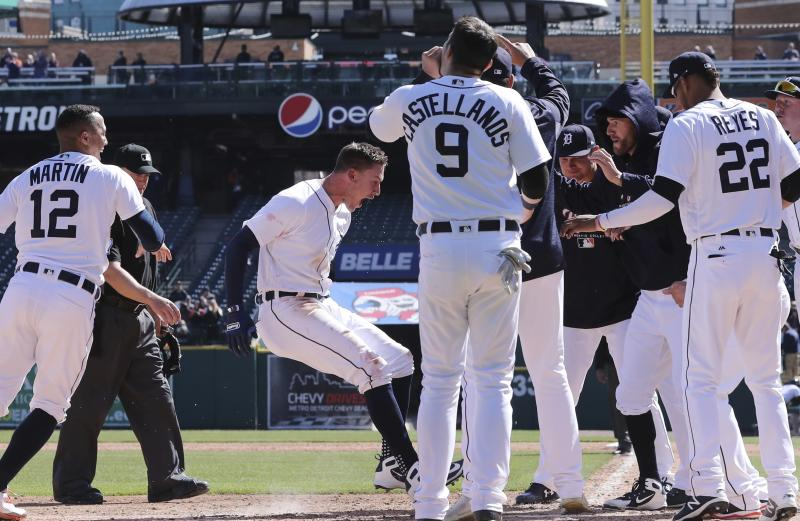 Teammates wait as Detroit Tigers' JaCoby Jones, center, touches home plate after his walkoff solo home run during the 10th inning of the first game of a baseball doubleheader against the Kansas City Royals, Friday, April 20, 2018, in Detroit. (AP Photo/Carlos Osorio)