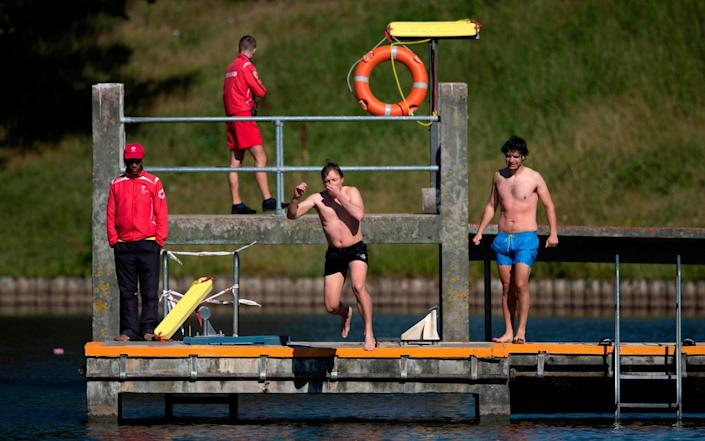 Swimmers jump into the water at the Hampstead Heath men's bathing pond after its reopening today - PA