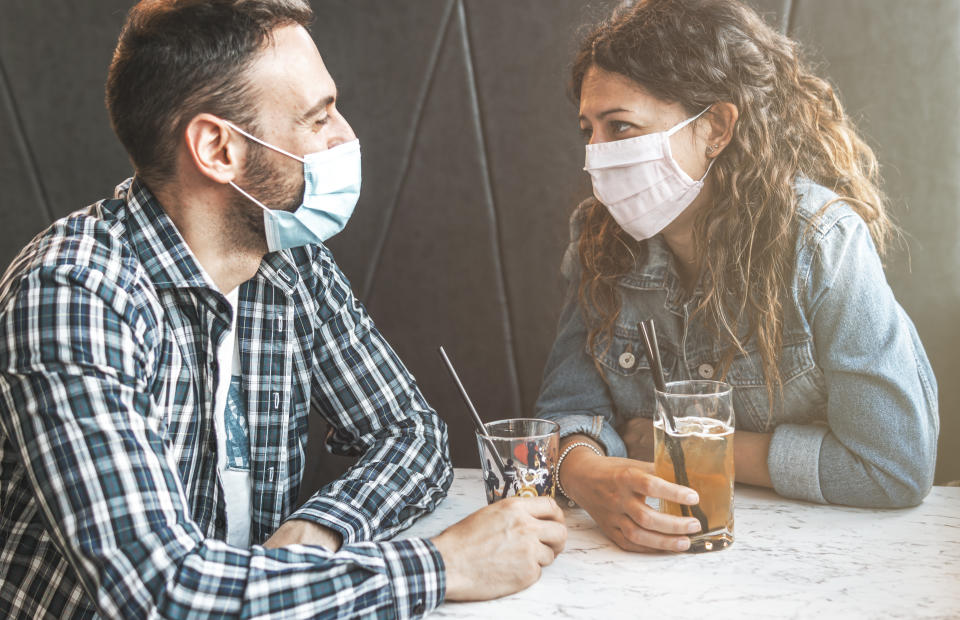 Engaged couple sitting in a caffe bar with surgical masks during the coronavirus pandemic - prevention and social distancing concept