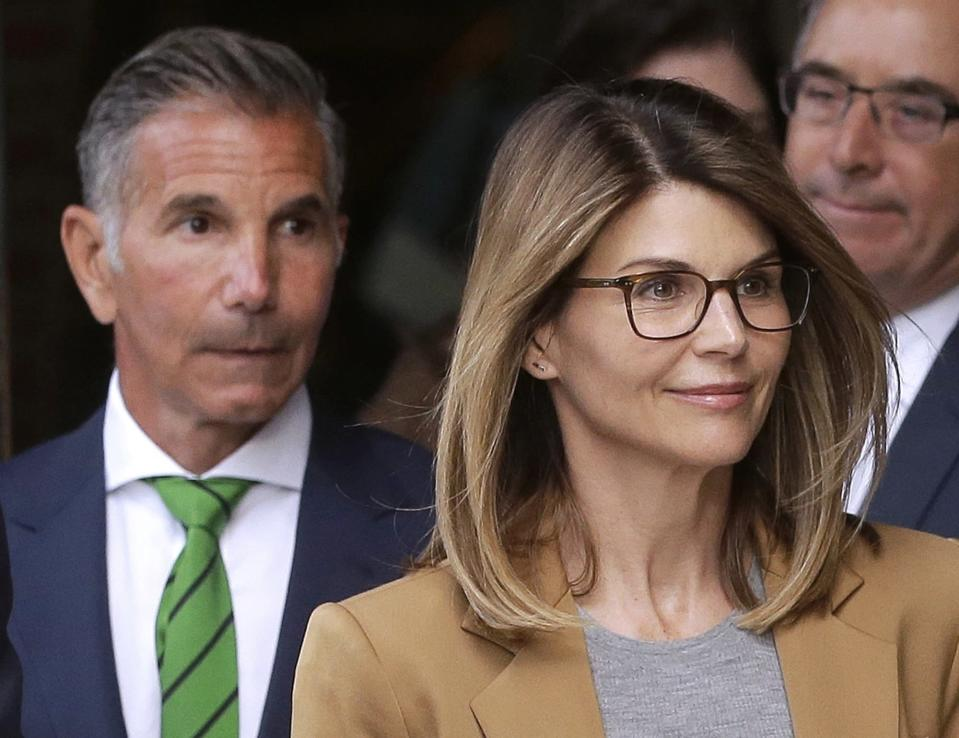 FILE - In this April 3, 2019, file photo, actress Lori Loughlin, front, and her husband, clothing designer Mossimo Giannulli, left, depart federal court in Boston after facing charges in a nationwide college admissions bribery scandal. Giannulli has been released from a California prison, Saturday, April 3, 2021 and is currently at a halfway house outside Los Angeles following his imprisonment for his role in a college admissions bribery scheme, records show. (AP Photo/Steven Senne, File)