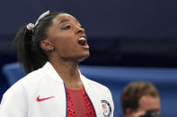 Simone Biles, of the United States, cheers for teammates after she exited the team final with apparent injury, at the 2020 Summer Olympics, Tuesday, July 27, 2021, in Tokyo. The 24-year-old reigning Olympic gymnastics champion Biles huddled with a trainer after landing her vault. She then exited the competition floor with the team doctor. (AP Photo/Ashley Landis)