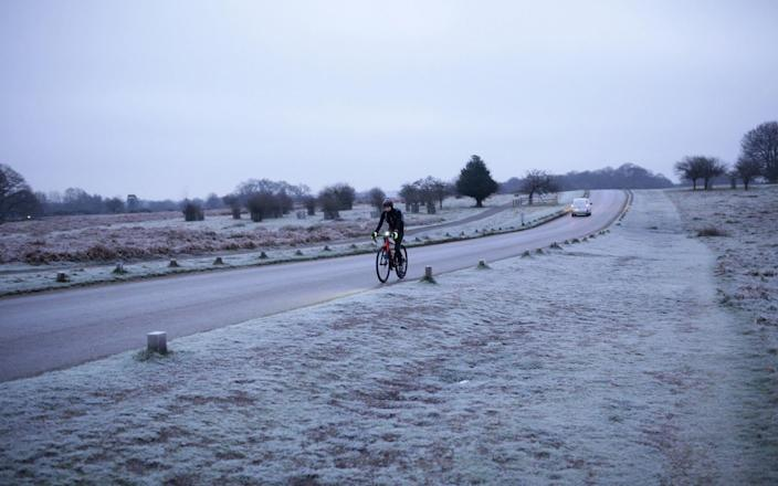A cyclist riding along a frost-covered Richmond Park, in south west London, during a cold start to the day in the capital - Yui Mok/PA