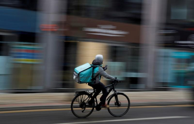 FILE PHOTO: A deliveroo delivery driver cycles through the centre of Manchester