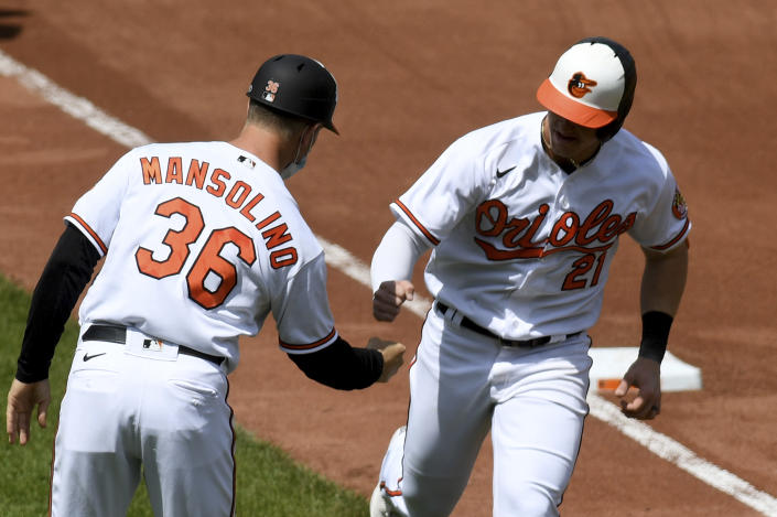 Baltimore Orioles' Austin Hays (21) celebrates with third base coach Tony Mansolino (36) after hitting a two-run home run against the Oakland Athletics in the fourth inning of a baseball game, Sunday, April 25, 2021, in Baltimore. (AP Photo/Will Newton)