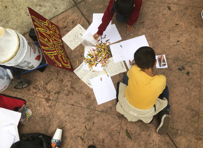 FILE - In this Thursday, Sept. 26, 2019 file photo, A Mexican boy draws with crayons while his family waits in Tijuana, Mexico, for their names to be called from a waiting list to claim asylum at a border crossing in San Diego. A federal judge ruled Thursday, Sept. 2, 2021 that the U.S. government's practice of denying migrants a chance to apply for asylum on the Mexican border until space opens up to process claims is unconstitutional.(AP Photo/Elliot Spagat, File)