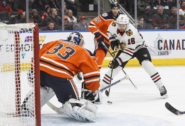 Chicago Blackhawks' Marcus Kruger (16) moves in on Edmonton Oilers goalie Cam Talbot (33) during the first period of an NHL hockey game Tuesday, Feb. 5, 2019, in Edmonton, Alberta. (Jason Franson/The Canadian Press via AP)