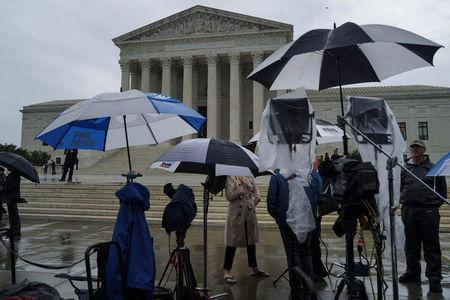 Television reporters wait prior to the U.S. Supreme Court's decision to impose limits on the ability of police to obtain cellphone data pinpointing the past location of criminal suspects, outside the U.S. Supreme Court in Washington, U.S., June 22, 2018. REUTERS/Toya Sarno Jordan
