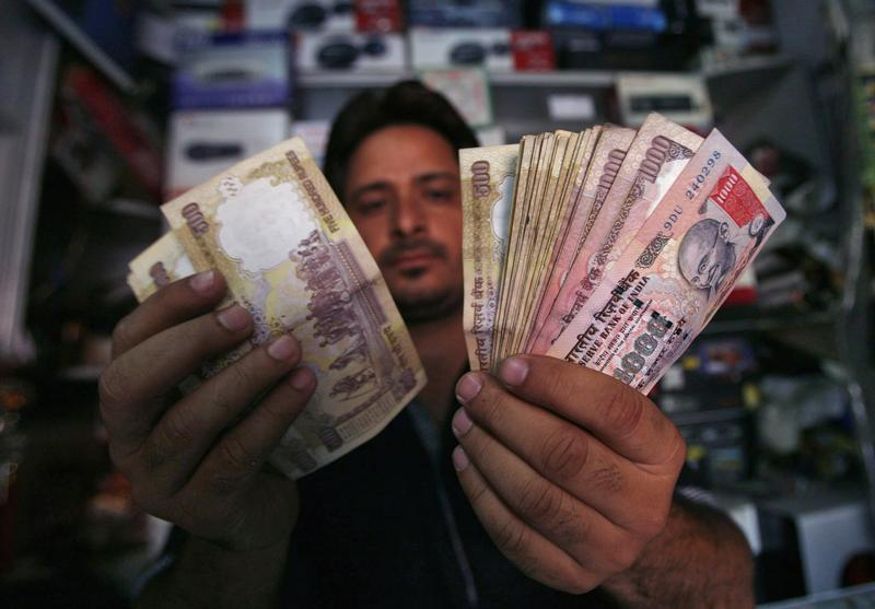 A shopkeeper poses for a picture as he counts Indian currency notes at his shop in Jammu