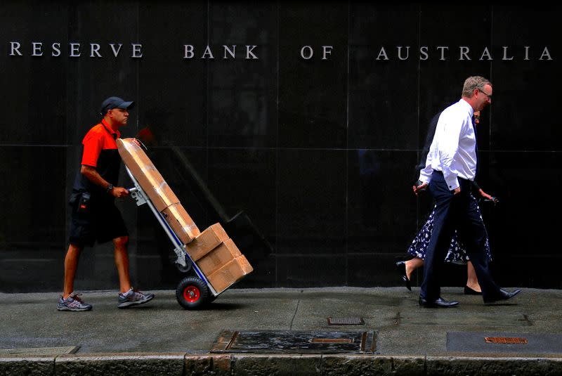 FILE PHOTO: A worker pushing a trolley walks with pedestrians past the Reserve Bank of Australia (RBA) head office in central Sydney