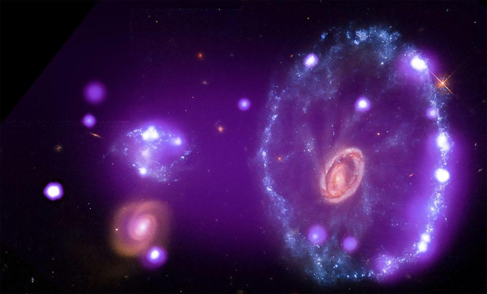 """<p>This image of the cyclonic <a href=""""https://www.popularmechanics.com/space/deep-space/a32109712/how-many-galaxies/"""" rel=""""nofollow noopener"""" target=""""_blank"""" data-ylk=""""slk:Cartwheel Galaxy"""" class=""""link rapid-noclick-resp"""">Cartwheel Galaxy</a> tells the celestial tale in which one galaxy plowed right through another. This intergalactic collision, in turn, generated a slew of new stars and hot gases (seen here in purple).</p>"""